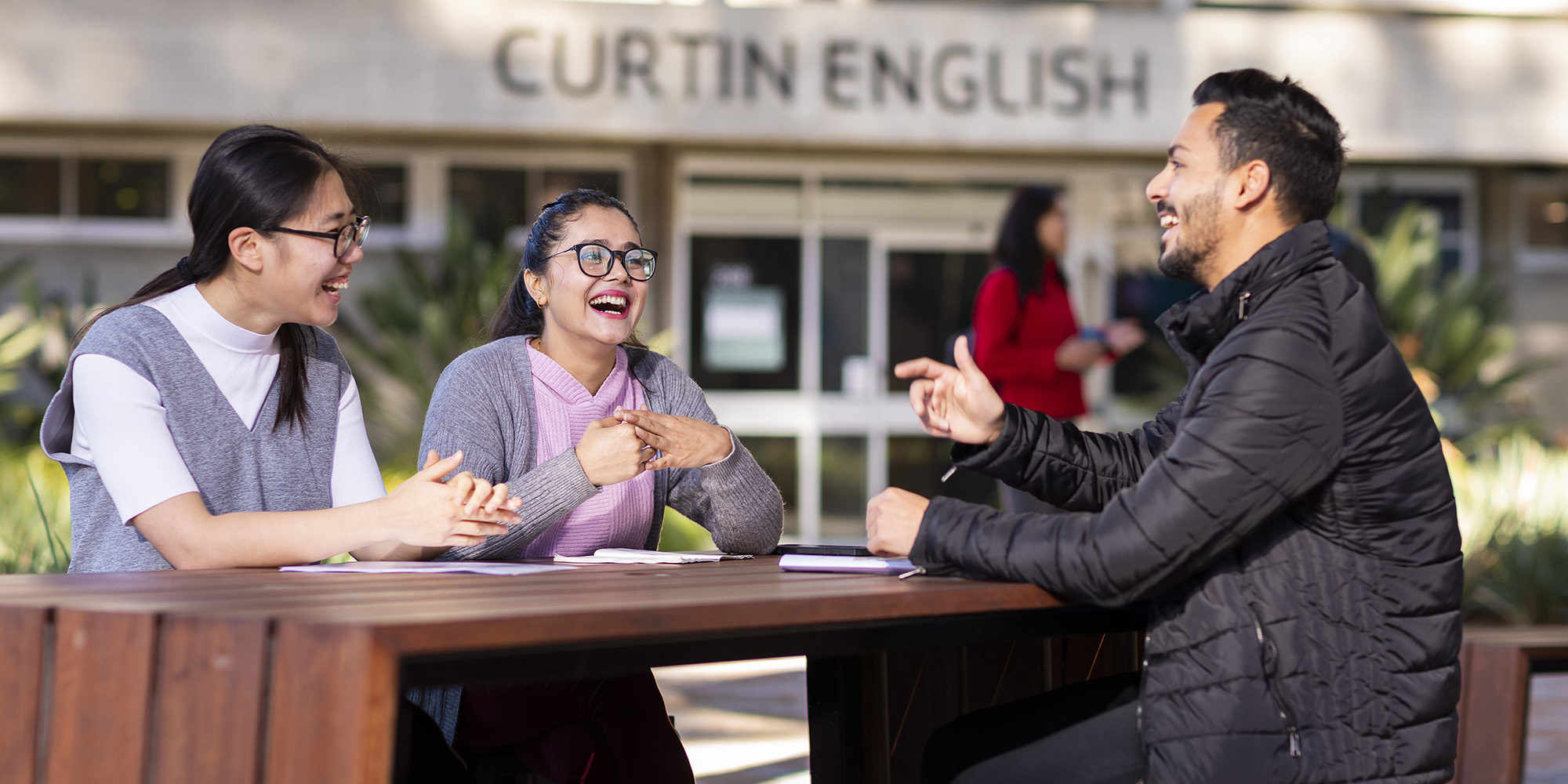 Two female and one male student sitting at a table, talking and laughing