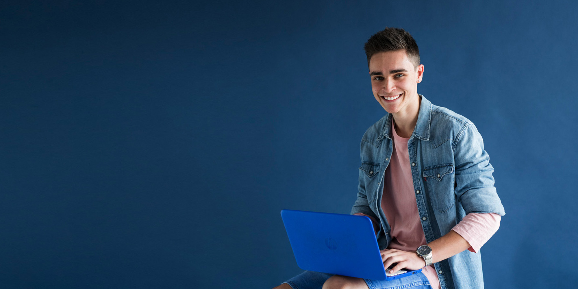 A young male sitting on a stool in front of a blue background, Holding a laptop