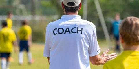Football coach wearing a white shirt which reads 'coach'