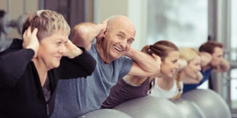 Elderly man exercising on a fitness ball in a group.