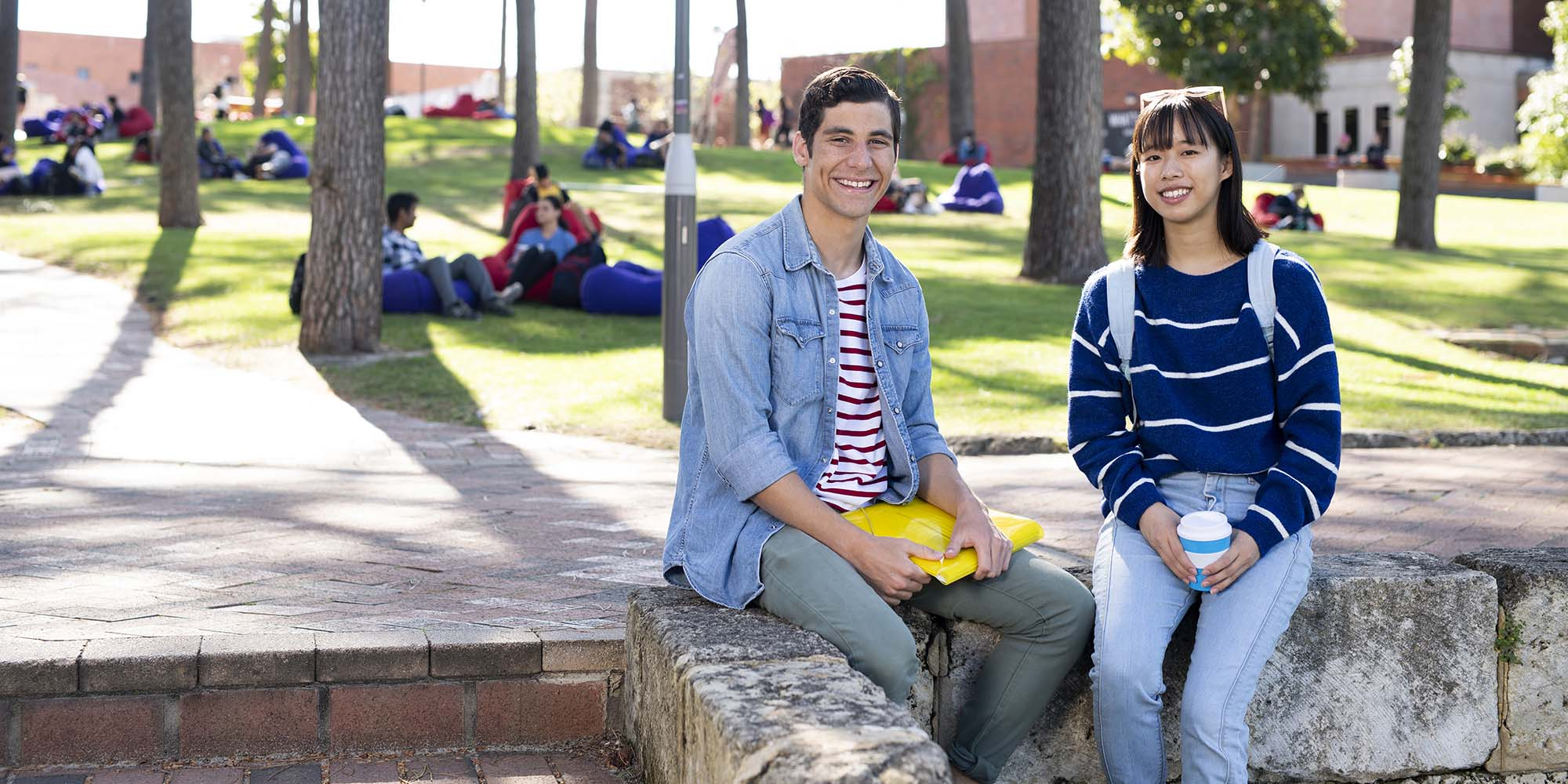 Male and female student sitting outside at Curtin Perth