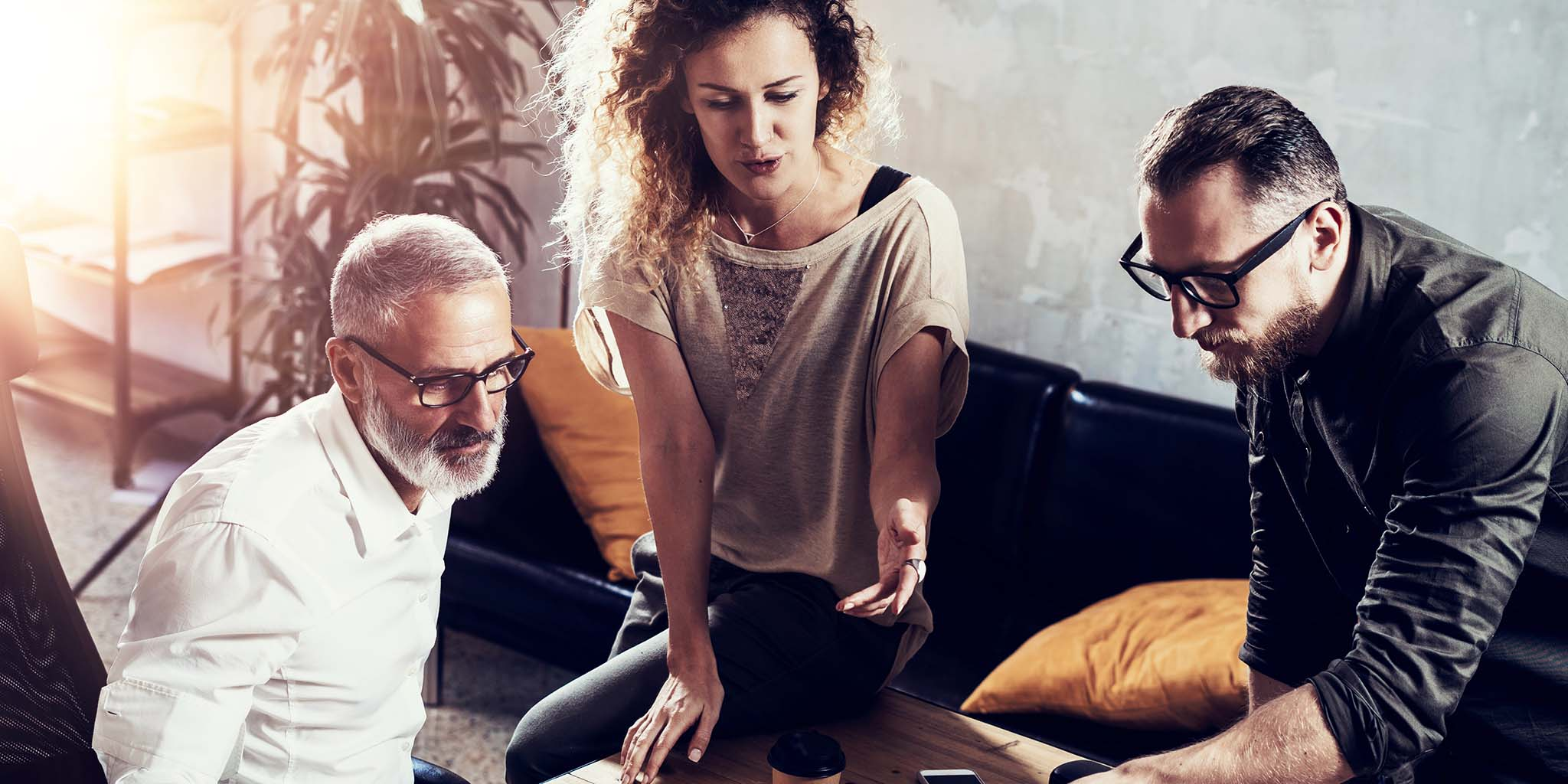 Young team of successful businessman found a great creative solution in modern coworking studio.Bearded man talking with colleagues about startup project.Business people brainstorm concept.